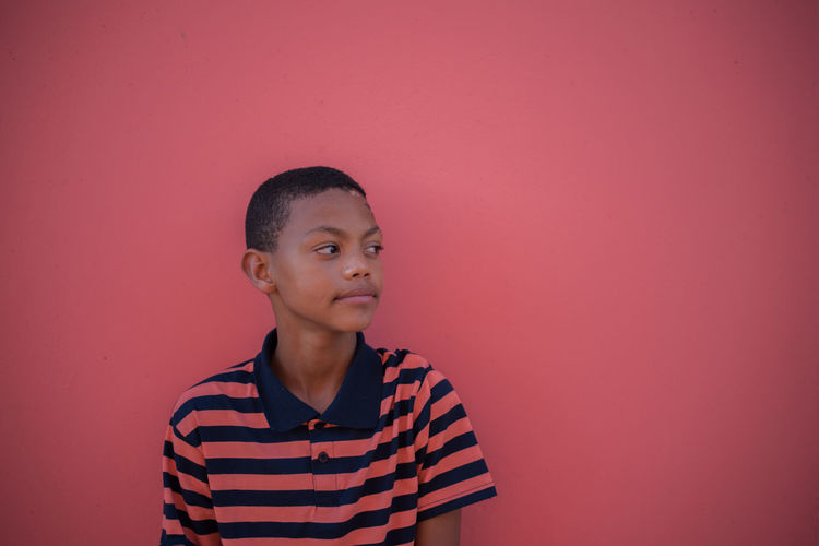 Boy standing against pink background