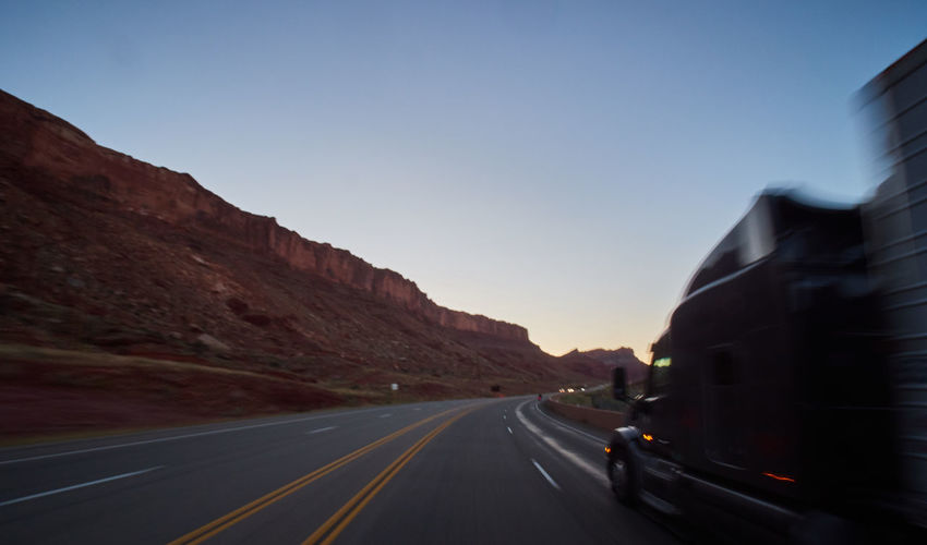 Road passing through mountains against clear sky