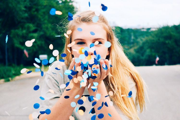 Close-Up Portrait Of Woman Blowing Confetti