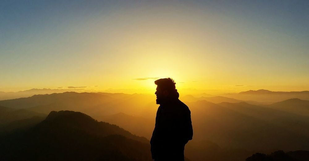 Silhouette man looking at mountain against sky during sunset