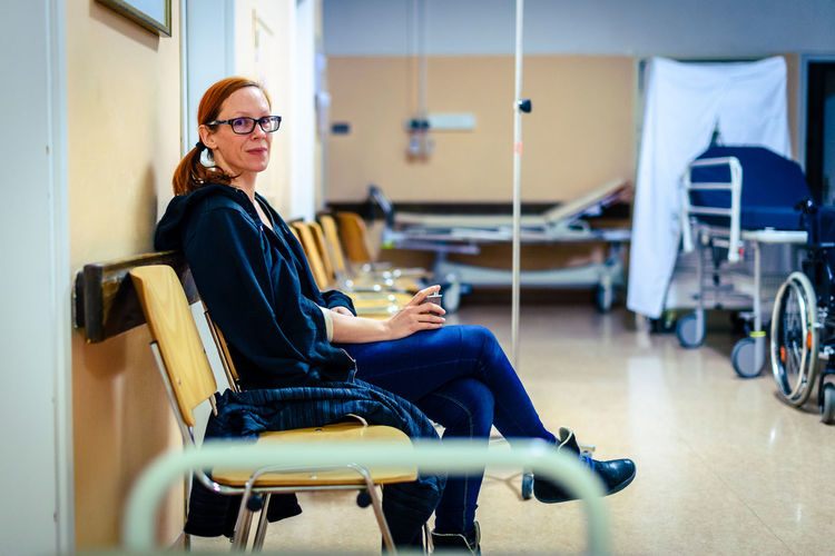 Patient sitting in hospital ward hallway waiting room with iv. Woman with intravenous therapy in her hand is waiting in the clinic corridor with blurred medical personnel in background. Emergency Hospital InFusion Intravenous Therapy Medicine Ward Woman Concept Cure Desease Health Care Health Care And Medical Healthy Eating Healthy Lifestyle Ill Indoors  Intravenous Intravenous Drip Iv Drip Medical Patient Real People Sickness Sitting Women