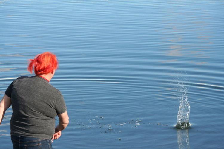 Woman Throwing Pebble In Blue Water