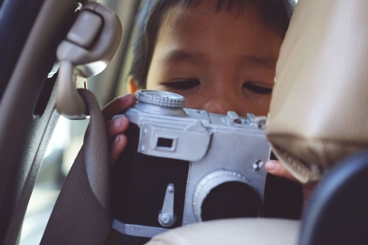 Close-up of boy photographing in car