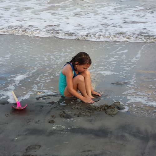 Girl sitting on shore at beach