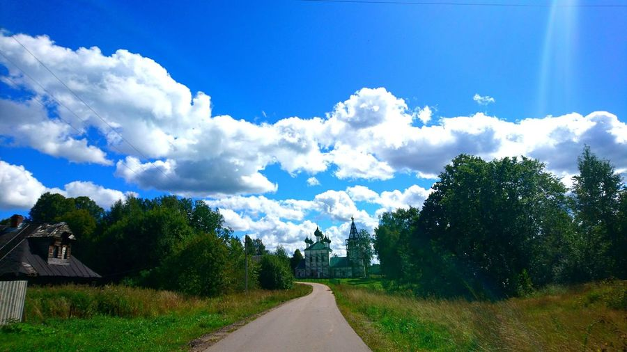 Road amidst trees against blue sky