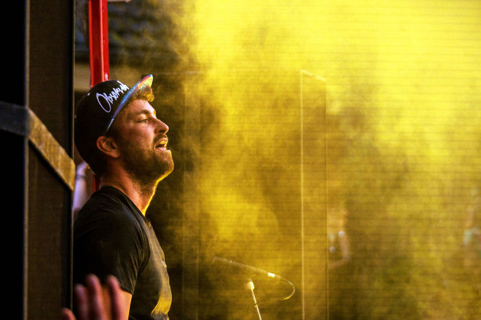 Rapper Marteria (Marten Laciny, born in Rostock, Germany) performs at a concert against right-wing extremism in Anklam, Germany. 8-23-2016. Agameoftones Band Cap Concert Concert Photography Concerts Day Eye4photography  EyeEm Best Shots Fog Germany Headwear Light And Shadow Marteria Music Music Festival One Person People Rap Rapper Shadows & Lights Stage Stage Light Stagephotography Yellow Resist EyeEm Diversity