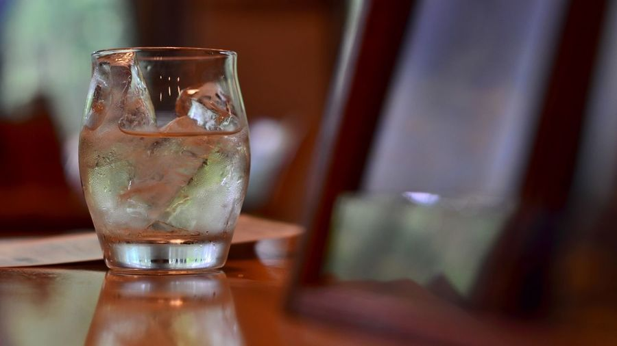 Glass of whisky and ice cubes on wooden table