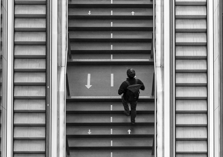 Low angle view of man walking on staircase of building