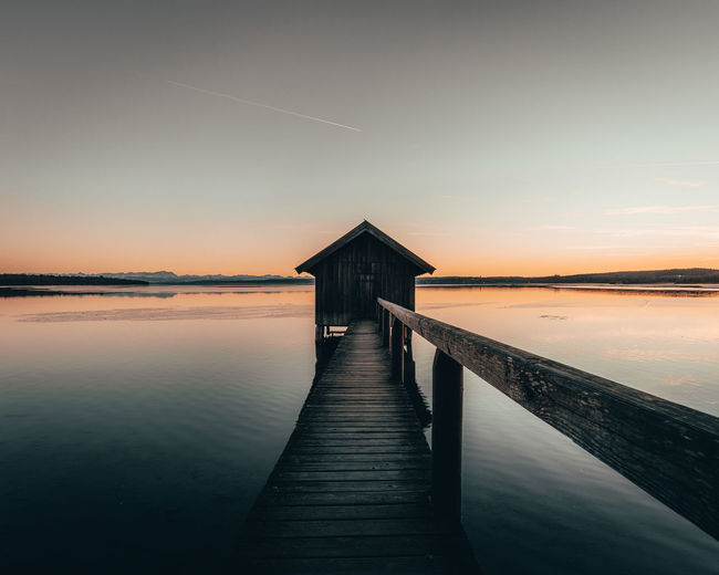 Pier and log cabin over sea against sky during sunset