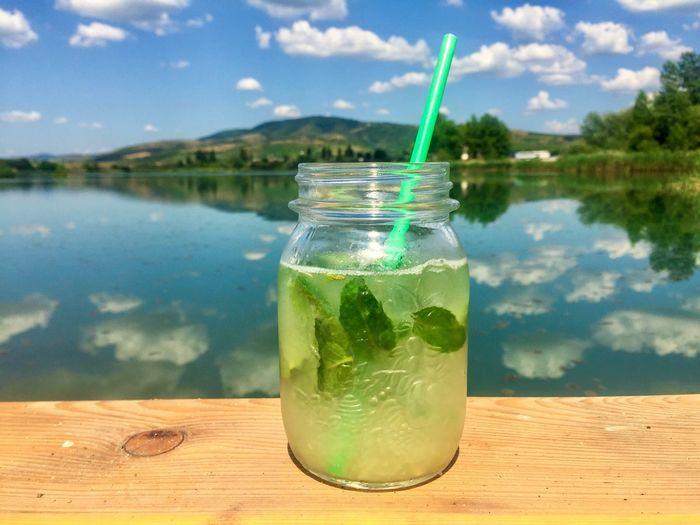 Jar of mint lemonade with drinking straw on wooden pontoon near the lake