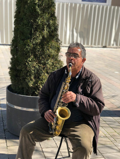 Male Street Musician Playing Saxophone On Footpath