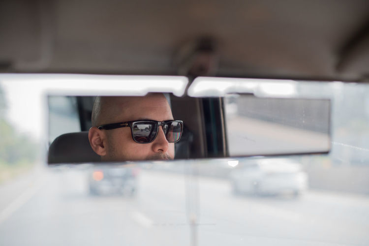 Reflection of man on rear-view mirror of car