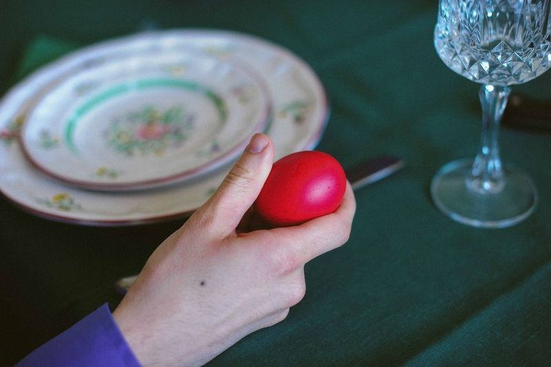 Cropped Image Of Person Holding Red Easter Egg At Table