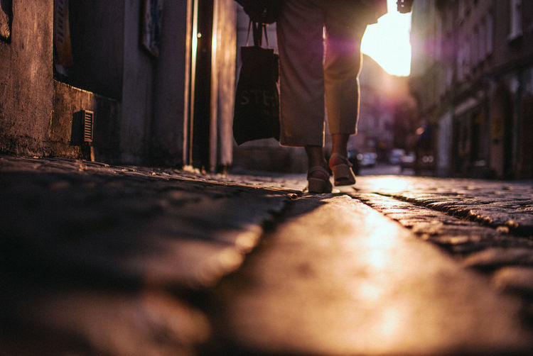 Low section of woman carrying shopping bag while walking on footpath during sunset