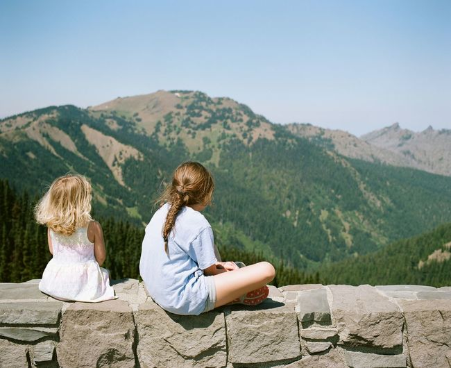 Rear View Of Girls Sitting On Stone Wall Against Mountain