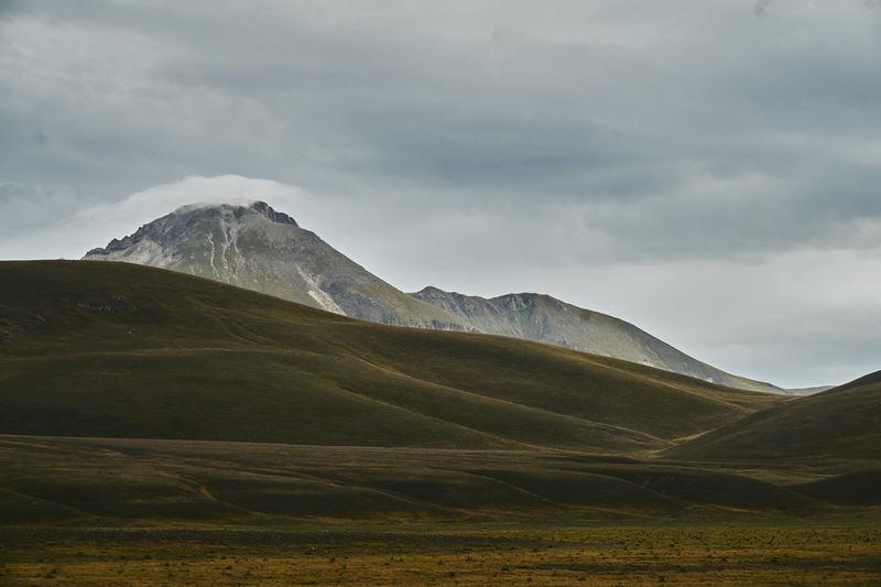 Idyllic shot of landscape against cloudy sky
