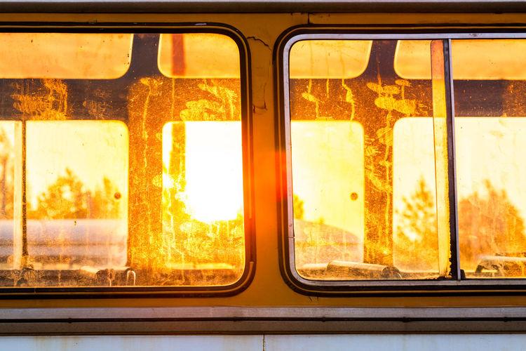 Old bus seen through window with golden sunlight behind