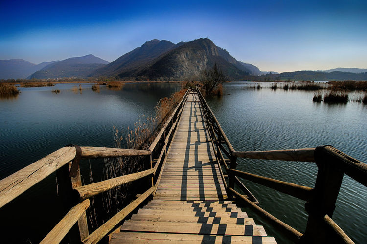 Footbridge over lake leading towards mountains