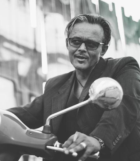 Man wearing eyeglasses riding motor scooter
