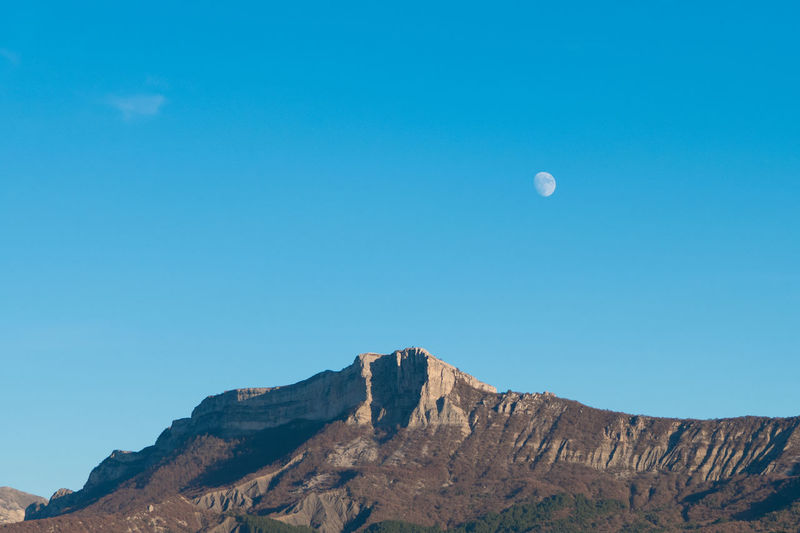 Low angle view of rock formation against clear blue sky with moon