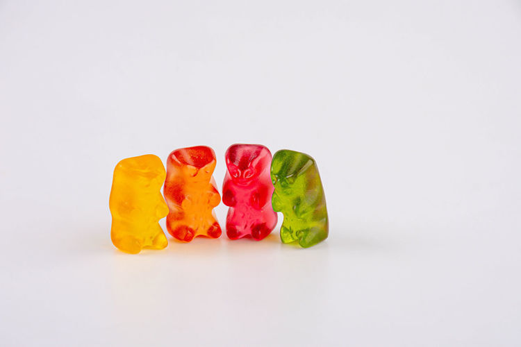 Close-up of multi colored candies against white background