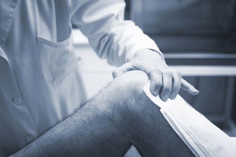 Midsection of doctor examining patient knee in hospital