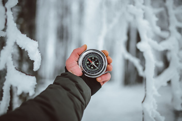Cropped hand of man holding navigational compass during winter