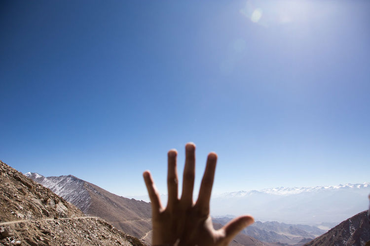 Cropped hand of person gesturing against mountains and sky during sunny day