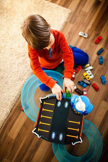 High angle view of boy playing with toy at home