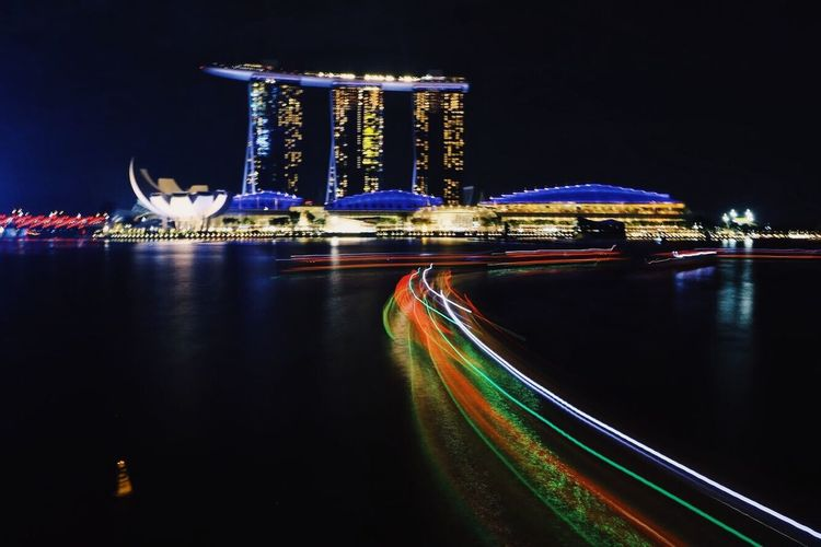 Light trails on river with marina bay sands in background at night
