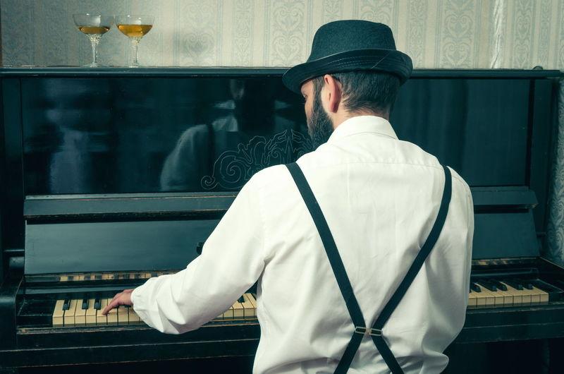 Rear View Of Man Playing Piano At Home