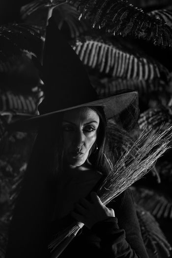 Close-up of mid adult woman in witch costume standing outdoors during halloween