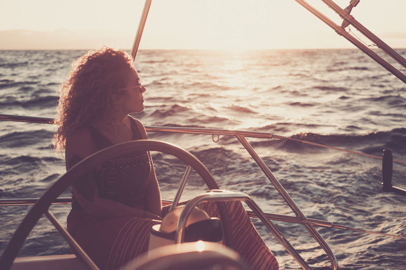 Woman sitting on boat sailing in sea against sky