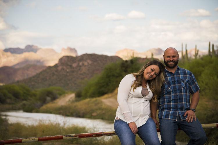 Portrait Of Smiling Couple Sitting On Fence