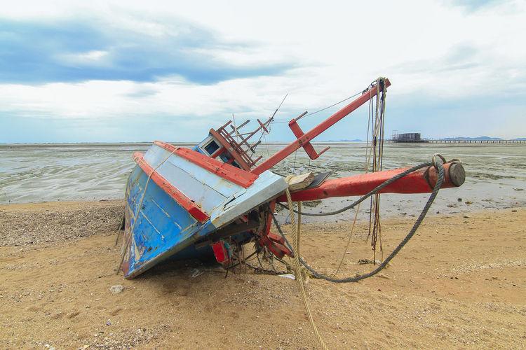 Abandoned ship moored on beach against sky