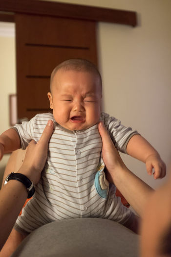 Cropped Close-up Of Parent Holding Baby Crying