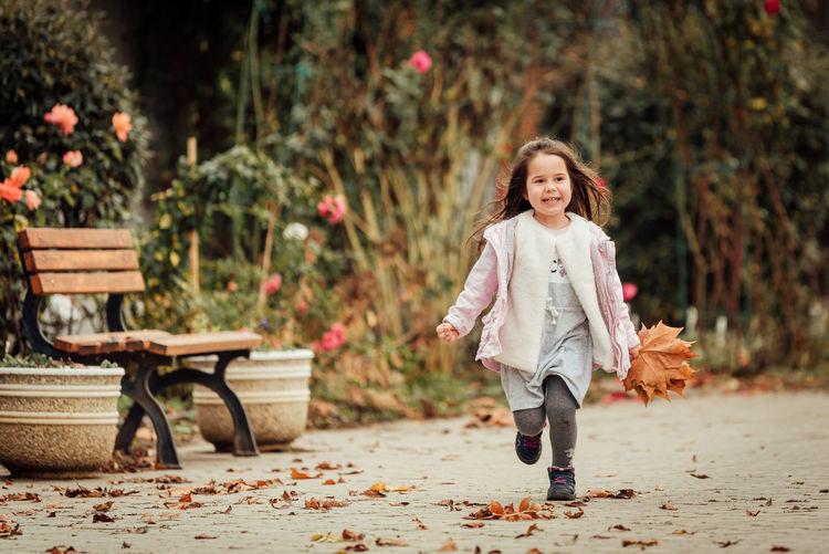 Full length of smiling girl running at park