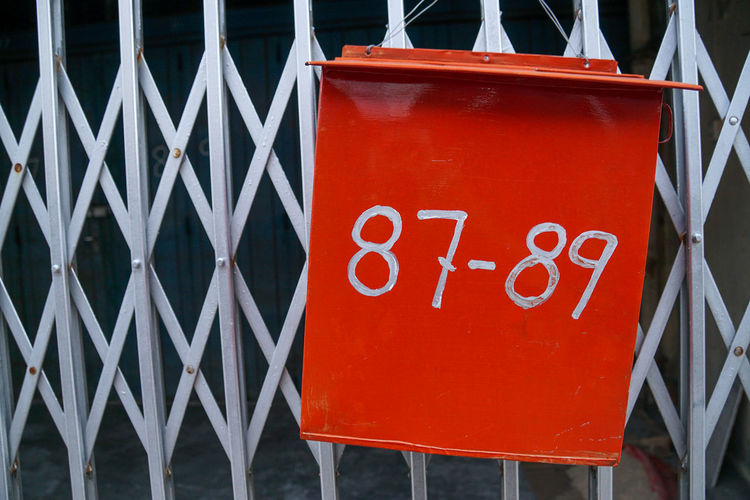 Close-up of red signboard against fence