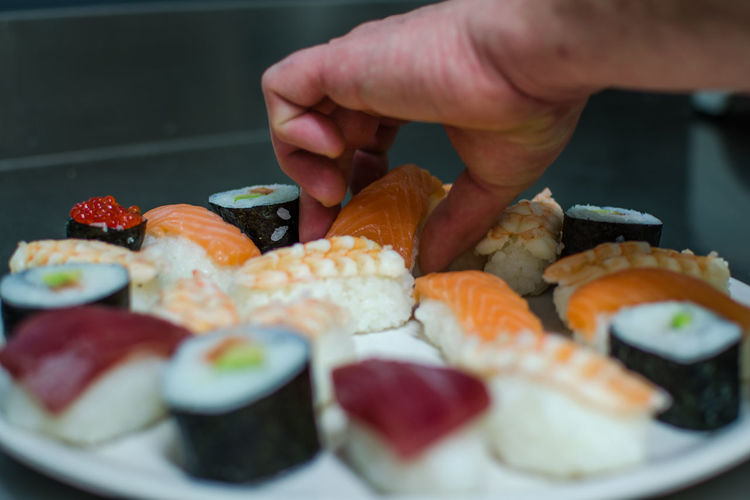 Cropped image of person preparing sushi