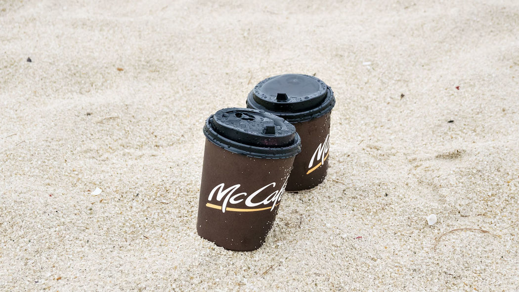 plastic cup on sand at beach Beach Close-up Coklat Day Drinks High Angle View McDonald's No People Outdoors Plastic Cup Sand