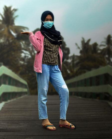 Full length of woman standing on walkway against sky
