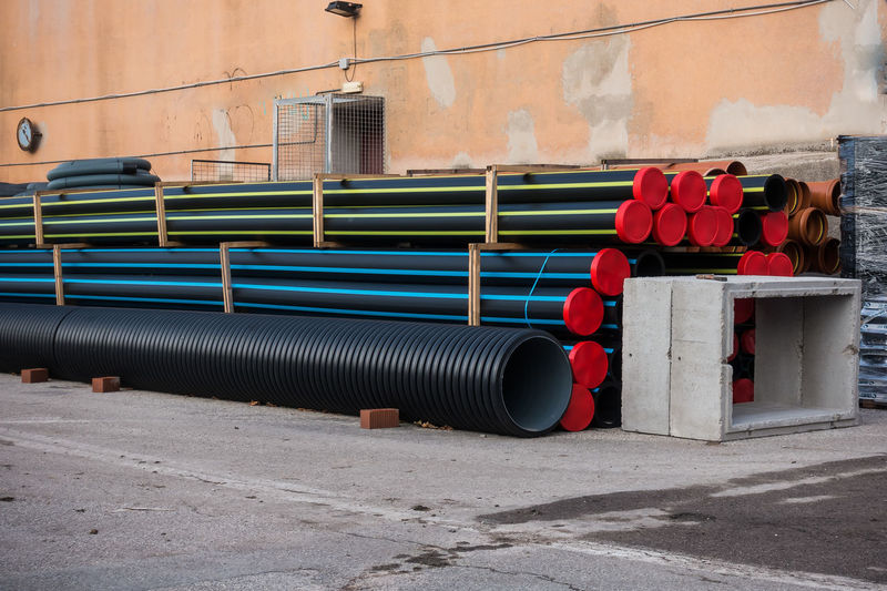 Stack of plastic pipes and prefabricated wells for road works. Day No People Red Metal Outdoors Transportation Industry Nature Empty Pipe - Tube Wall City Pipe Tube Roadwork Site Construction Plumbing Supply