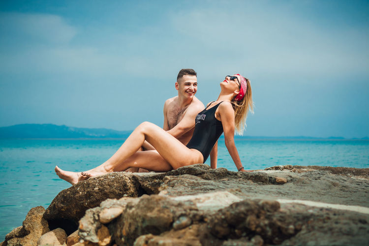 Young couple spending leisure time at beach against sky