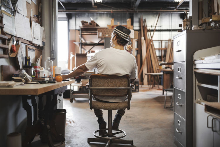 Rear view of man working in office