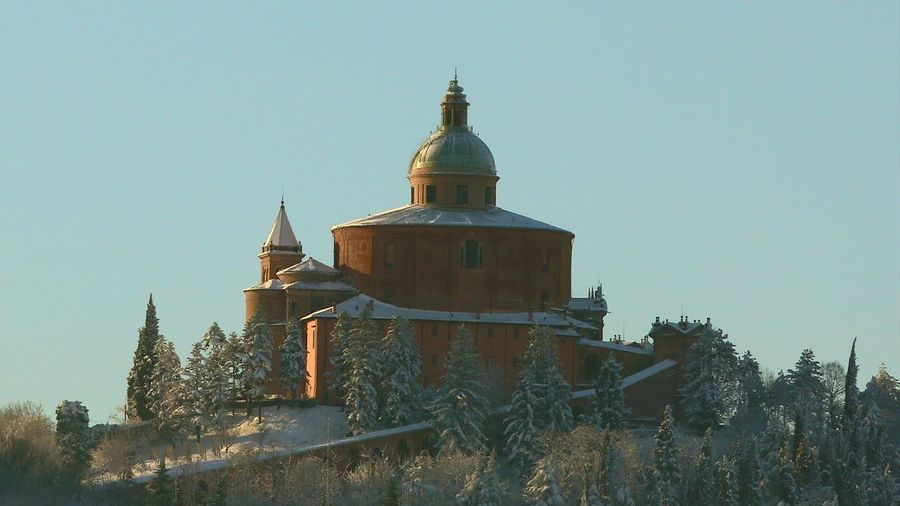distant close up of snowy San Luca basilica in a winter morning on Bologna hills in Italy. Bologna Bologna, Italy Italy San Luca San Luca's Church San Luca Bologna San Luca Skyline Church Cathedral Basilica Night Sunset Religion Dome Madonna Holy Mary Holy Virgin Madonna Di San Luca Dawn Snow Snowy Winter Sky Architecture Tree Built Structure Clear Sky Building Exterior Plant Nature Belief No People Building Place Of Worship Spirituality Day Low Angle View Outdoors Tower Spire