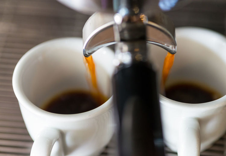 Coffee pouring in cups from espresso maker