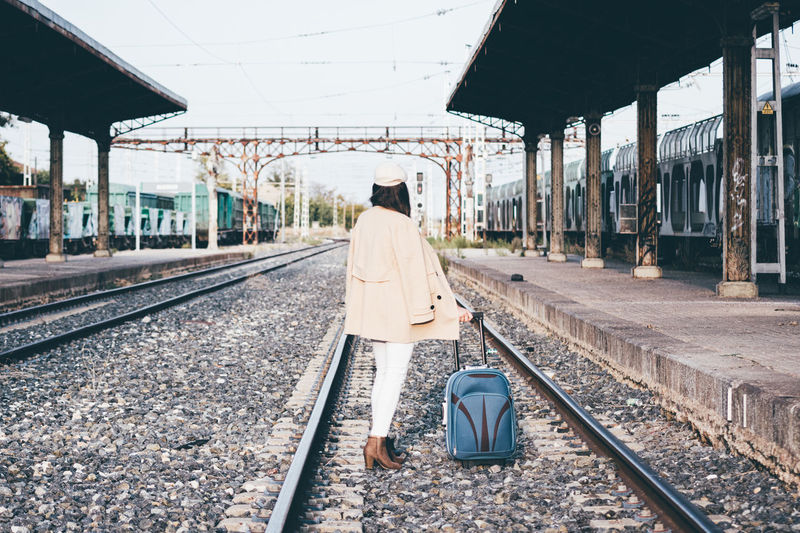 Woman with suitcase on railroad station platform