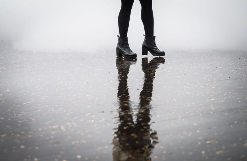 Low section of woman walking on wet street