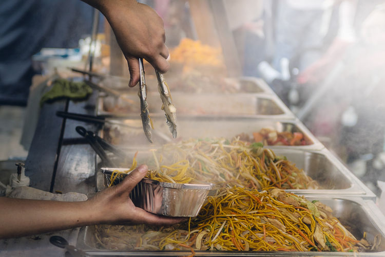 Midsection Of Hand Serving Noodles At Market Stall