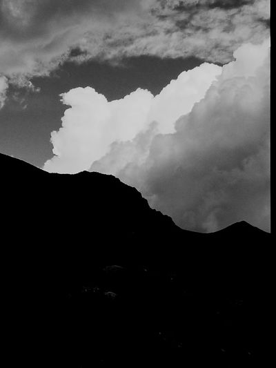 Low angle view of silhouette mountains against sky